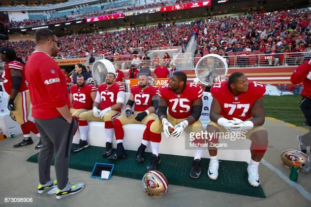 Joe Staley of the San Francisco 49ers talks with Erik Magnuson Brandon Fusco Daniel Kilgore Laken Tomlinson and Trent Brown on the sideline during...