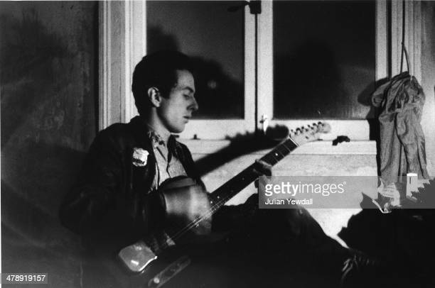 Joe Strummer of The Clash practices by lamplight at a squat in a disused ice cream factory in Foscote Mews London W9 1976 It was here that Strummer...