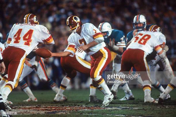 Joe Theismann of the Washington Redskins hands off to teammate John Riggins during Super Bowl XVII against the Miami Dolphins on January 30 1983 at...