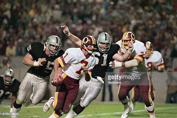 Joe Theismann of the Washington Redskins moments before being tackled by members of the Oakland Raiders during a Super Bowl game