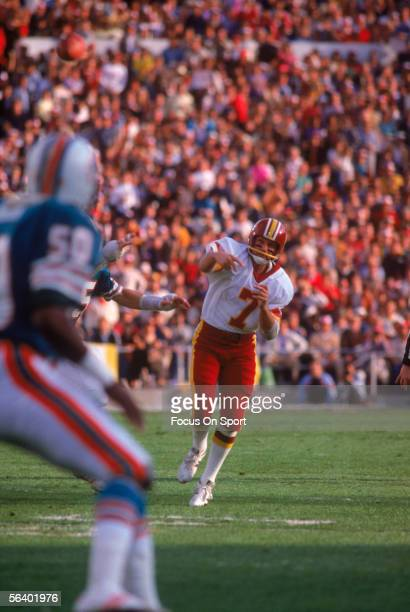 Joe Theismann of the Washington Redskins passes against the Miami Dolphins during Super Bowl XVII at the Rose Bowl on January 30 1983 in Pasadena...