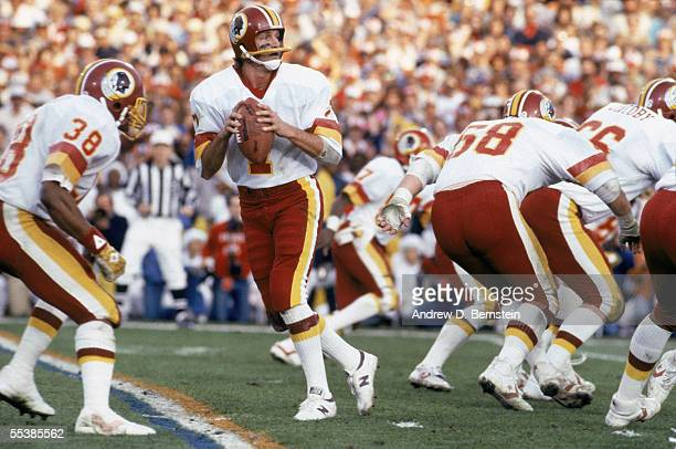 Joe Theismann of the Washington Redskins rolls out to pass against the Miami Dolphins during Super Bowl XVII on January 30 1983 at the Rose Bowl in...