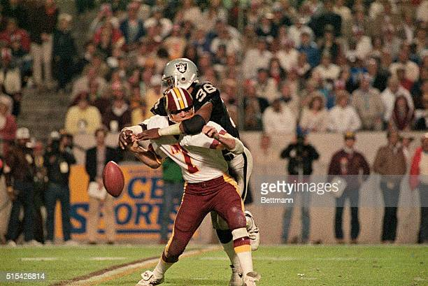 Joe Theismann of the Washington Redskins tackled by a member of the Oakland Raiders during Super Bowl game