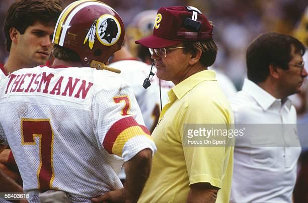 Joe Theismann of the Washington Redskins talks to head coach Joe Gibbs during Super Bowl XVII against the Miami Dolphins at the Rose Bowl on January...