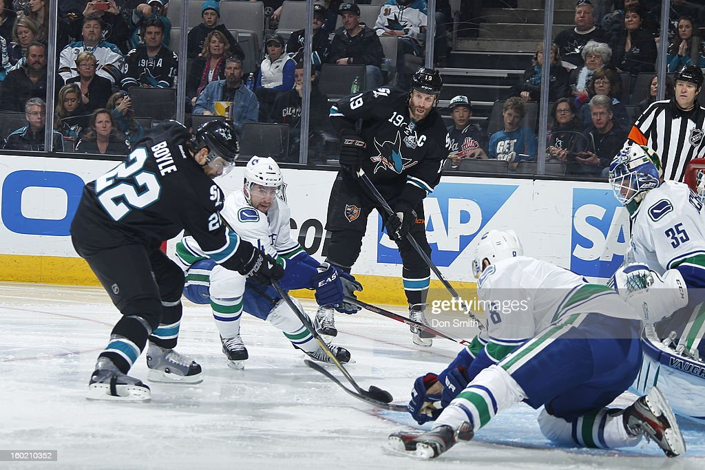 Joe Thornton #19 and Dan Boyle #22 of the San Jose Sharks look to score against Keith Ballad #4, Christopher Tanev #8 and Cory Schneider #35 of the Vancouver Canucks during an NHL game on January 27, 2013 at HP Pavilion in San Jose, California.