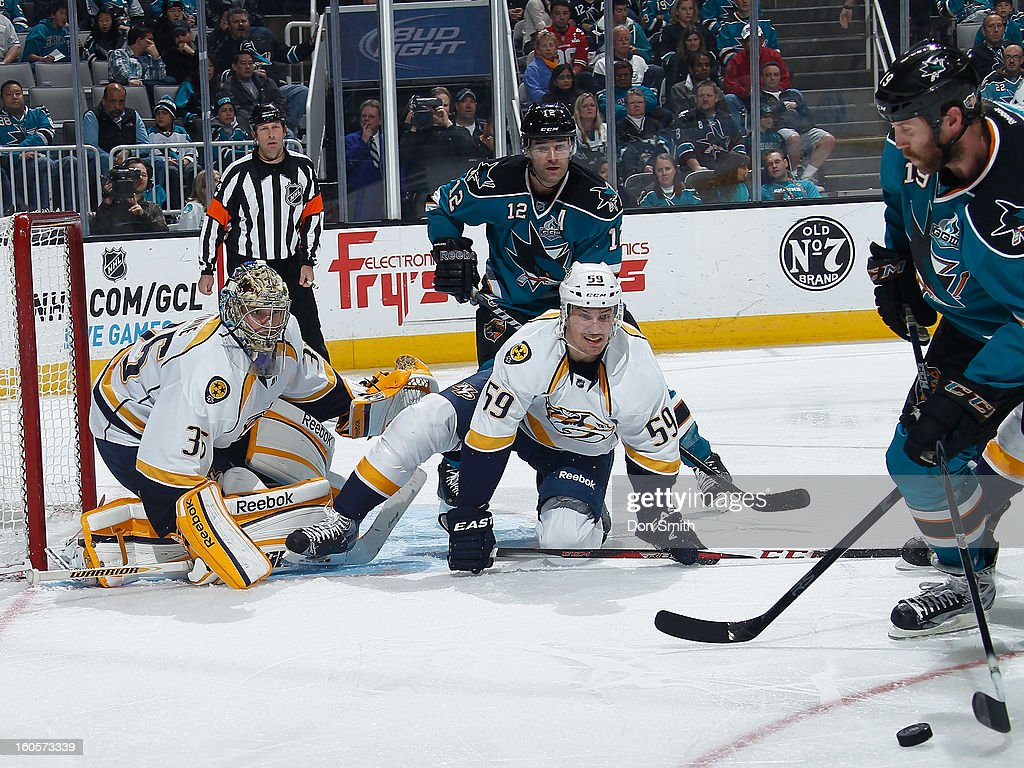 Joe Thornton #19 and Patrick Marleau #12 of the San Jose Sharks try to score against Pekka Rinne #35 and Roman Josi #59 of the Nashville Predators during an NHL game on February 2, 2013 at HP Pavilion in San Jose, California.