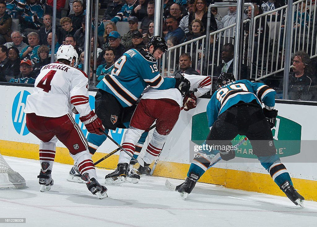 Joe Thornton #19 and Ryane Clowe #29 of the San Jose Sharks fight for the puck against Zbynek Michalek #4 and a member of the Phoenix Coyotes during an NHL game on February 9, 2013 at HP Pavilion in San Jose, California.