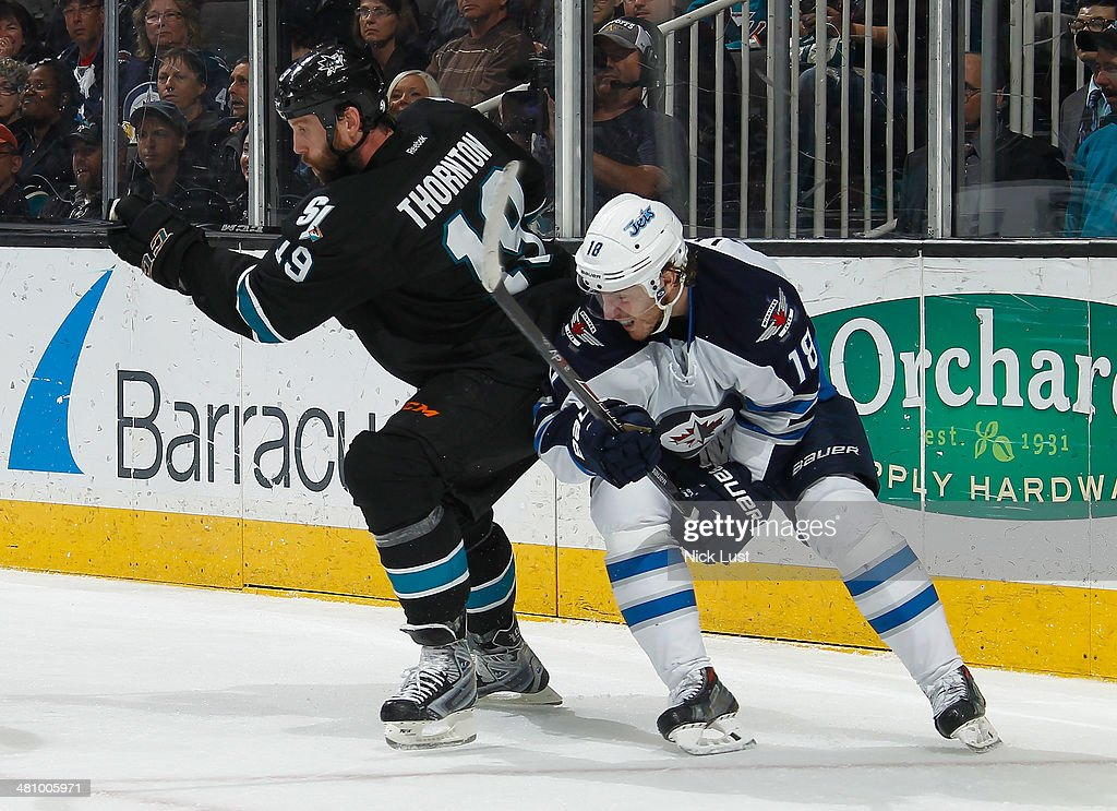 <a gi-track='captionPersonalityLinkClicked' href=/galleries/search?phrase=Joe+Thornton&family=editorial&specificpeople=201829 ng-click='$event.stopPropagation()'>Joe Thornton</a> #19 of the San Jose Sharks battles for the puck in his 1200th NHL game against <a gi-track='captionPersonalityLinkClicked' href=/galleries/search?phrase=Bryan+Little&family=editorial&specificpeople=540533 ng-click='$event.stopPropagation()'>Bryan Little</a> #18 of the Winnipeg Jets during an NHL game on March 27, 2014 at SAP Center in San Jose, California.