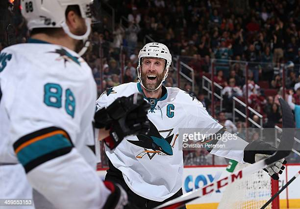 Joe Thornton of the San Jose Sharks celebrates with Brent Burns after Burns scored a third period goal against the Phoenix Coyotes during the NHL...
