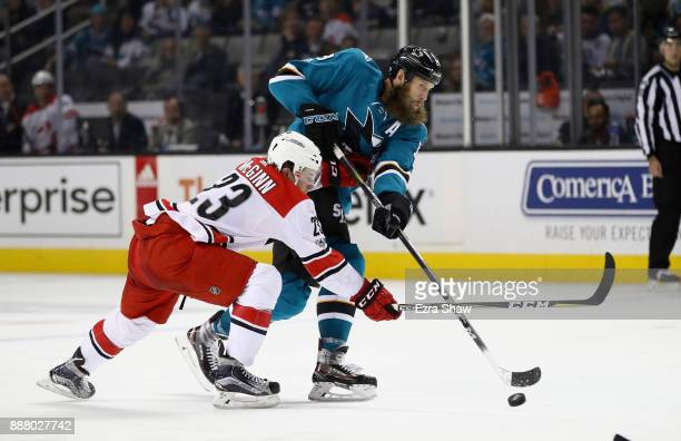 Joe Thornton of the San Jose Sharks passes the puck away from Brock McGinn of the Carolina Hurricanes at SAP Center on December 7 2017 in San Jose...
