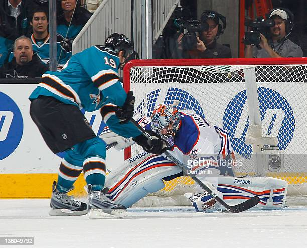 Joe Thornton of the San Jose Sharks scores a goal against Nikolai Khabibulin of the Edmonton Oilers at HP Pavilion on December 17 2011 in San Jose...
