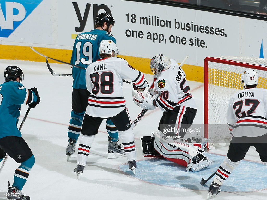 Joe Thornton #19 of the San Jose Sharks tries to score against Corey Crawford #50 and Patrick Kane #88 of the Chicago Blackhawks during an NHL game on February 1, 2014 at SAP Center in San Jose, California.