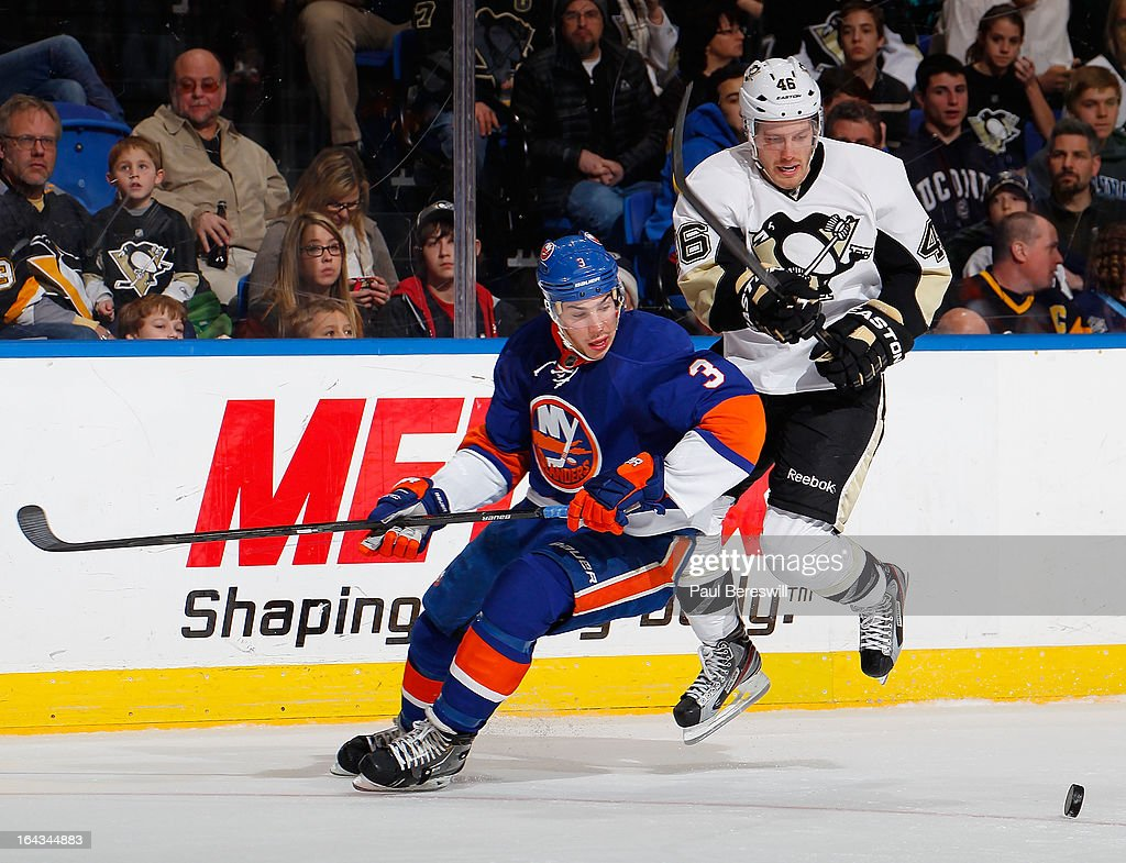 Joe Vitale #46 of the Pittsburgh Penguins and Travis Hamonic #3 of the New York Islanders keep their eyes on the puck in an NHL hockey game at Nassau Veterans Memorial Coliseum on March 22, 2013 in Uniondale, New York.