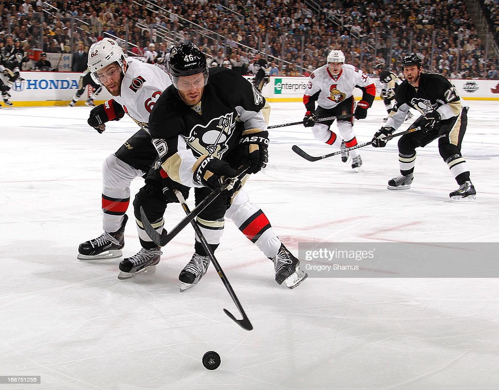 Joe Vitale #46 of the Pittsburgh Penguins battles for the loose puck against Eric Gryba #62 of the Ottawa Senators in Game One of the Eastern Conference Semifinals during the 2013 NHL Stanley Cup Playoffs at Consol Energy Center on May 14, 2013 in Pittsburgh, Pennsylvania.