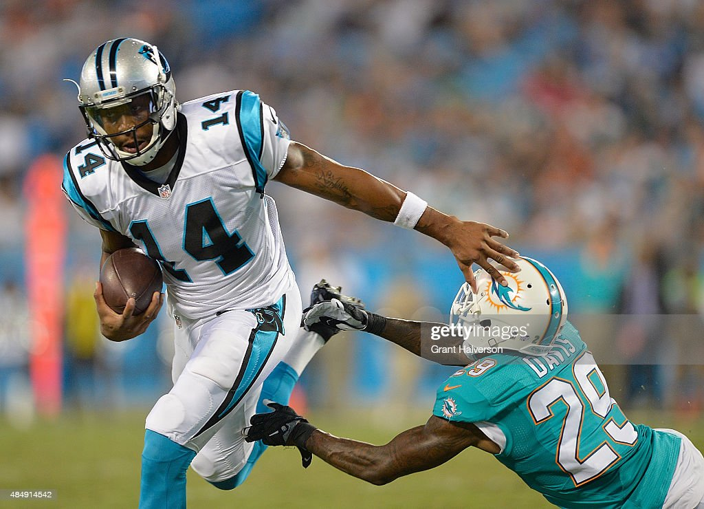Joe Webb #14 of the Carolina Panthers breaks away from Will Davis #29 of the Miami Dolphins during their preseason NFL game at Bank of America Stadium on August 22, 2015 in Charlotte, North Carolina.