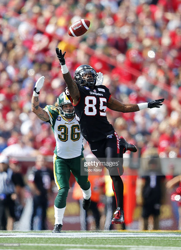 Joe West #85 of the Calgary Stampeders jumps to try and catch a pass in front of Aaron Grymes #36 of the Edmonton Eskimos in the first half of their CFL football game September 1, 2014 at McMahon Stadium in Calgary, Alberta, Canada.