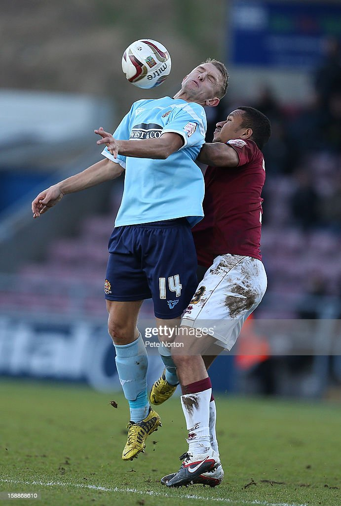 Joe Widdowson of Northampton Town contests the ball with Jake Reed #14 of Dagenham & Redbridge during the npower League Two match between Northampton Town and Dagenham & Redbridge at Sixfields Stadium on January 1, 2013 in Northampton, England.