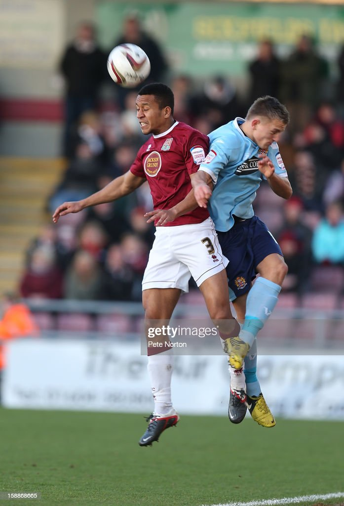 Joe Widdowson of Northampton Town heads the ball clear under pressure from Jake Reed of Dagenham & Redbridge during the npower League Two match between Northampton Town and Dagenham & Redbridge at Sixfields Stadium on January 1, 2013 in Northampton, England.