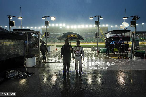 Joe Williams left crew chief for Sprint Cup Series driver JJ Yeley right walk off the track as a rain delay halts the SpongeBob SquarePants 400 race...