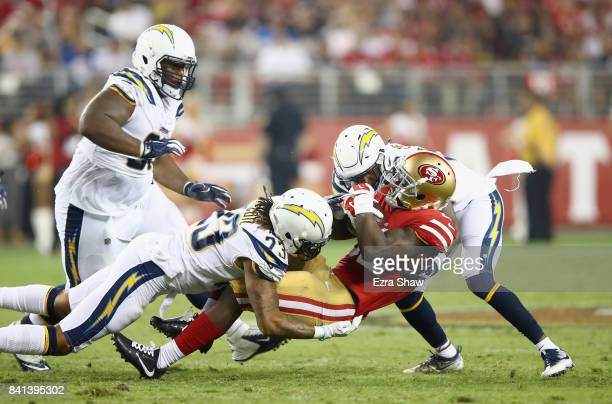 Joe Williams of the San Francisco 49ers is tacked by Dexter McCoil and Brandon Stewart of the Los Angeles Chargers at Levi's Stadium on August 31...
