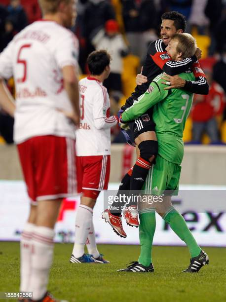 Joe Willis and Marcelo Saragosa of DC United celebrate after defeating the New York Red Bulls during the Eastern Conference Semifinals at Red Bull...
