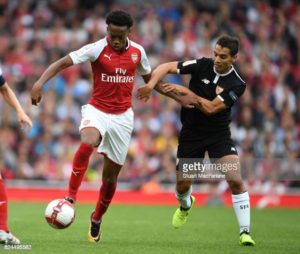 Joe Willock of Arsenal breaks past Wissam Ben Yedder of Seville during the Emirates Cup match between Arsenal and Seville at Emirates Stadium on July...