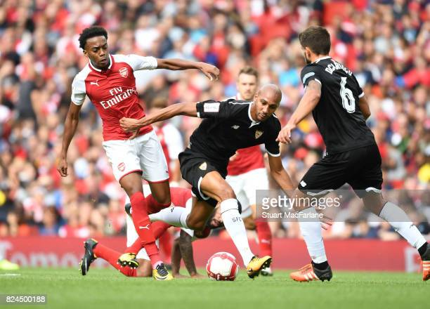 Joe Willock of Arsenal challenged by Steven N'Zonzi of Seville during the Emirates Cup match between Arsenal and Seville at Emirates Stadium on July...