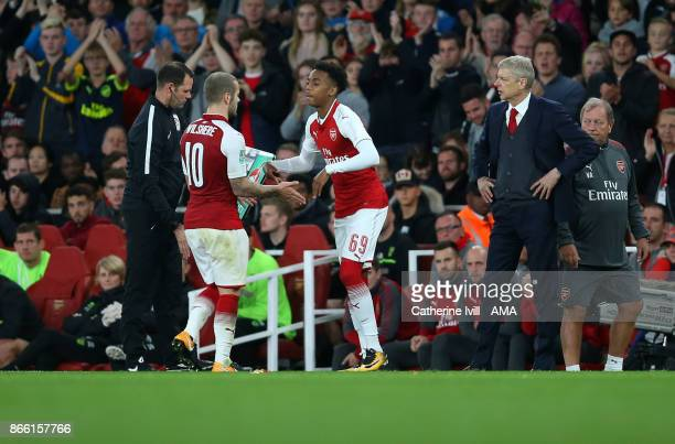 Joe Willock of Arsenal substitutes Jack Wilshere of Arsenal during the Carabao Cup Fourth Round match between Arsenal and Norwich City at Emirates...