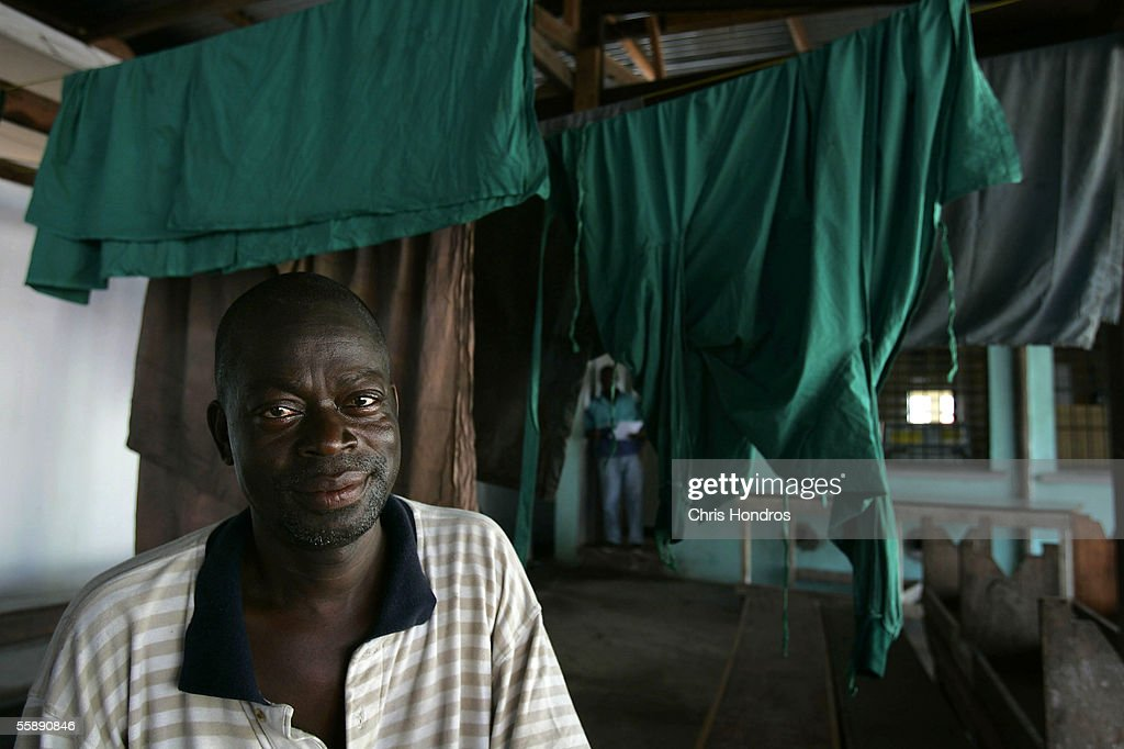 Joe Wilson, 45, sits in front of drying hospital gowns October 10, 2005 in Monrovia, Liberia. Wilson was working as a janitor and maintenence man at a Doctors Without Borders health clinic when intense fighting broke out in Monrovia in 2003. For six weeks, Wilson was pressed into service rescuing Liberians who lay injured in the streets around the clinic, which morphed into an ad hoc field hospital. 'I was just trying to help,' Wilson says. 'Everyday we brought in so many people.' Wilson now washes the laundry at Doctors Without Borders hospital in Monrovia.