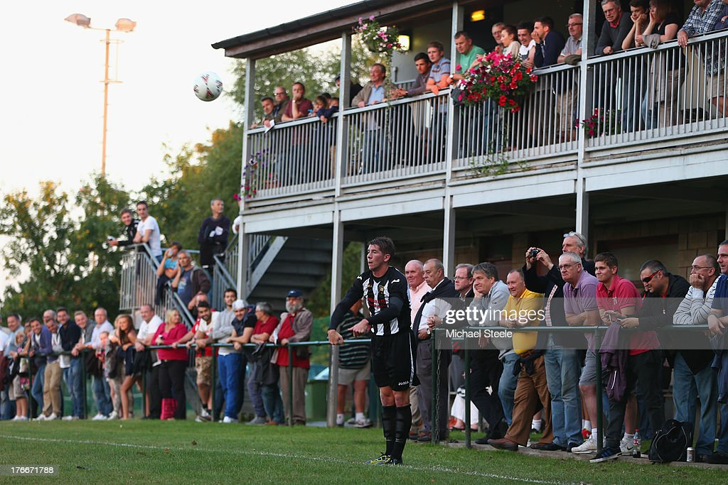 Joe Wright of Alresford Town takes a throw as supporters look on during the FA Cup Extra Preliminary Round match between Alresford Town and Winchester City at Alrebury Park on August 16, 2013 in New Alresford, England.