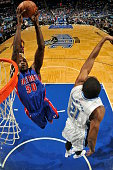 Joel Anthony of the Detroit Pistons goes to the basket against Maurice Harkless of the Orlando Magic on December 30 2014 at Amway Center in Orlando...