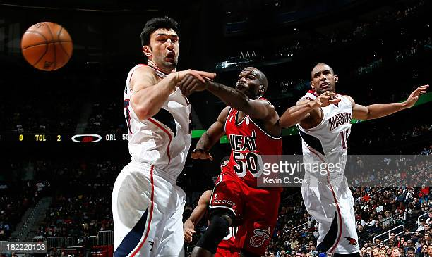Joel Anthony of the Miami Heat battles for a rebound against Zaza Pachulia and Al Horford of the Atlanta Hawks at Philips Arena on February 20 2013...