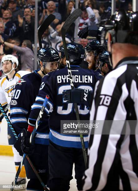 Joel Armia and Dustin Byfuglien of the Winnipeg Jets celebrate a third period goal by teammate Kyle Connor against the Nashville Predators at the MTS...
