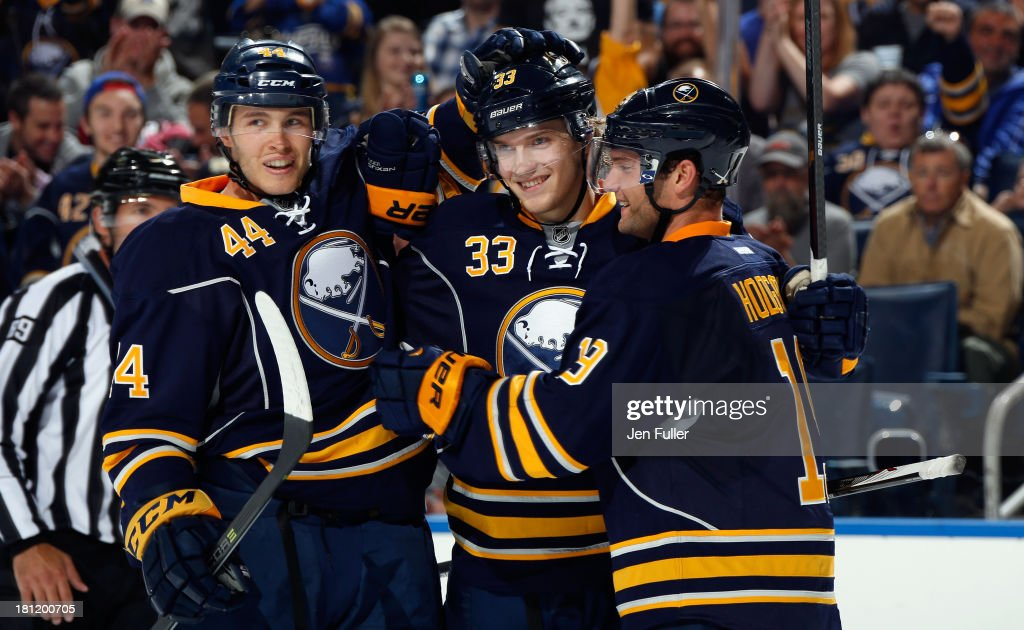 Joel Armia #33 of the Buffalo Sabres celebrates his second period goal against the Carolina Hurricanes with teammates <a gi-track='captionPersonalityLinkClicked' href=/galleries/search?phrase=Brayden+McNabb&family=editorial&specificpeople=4779653 ng-click='$event.stopPropagation()'>Brayden McNabb</a> #44 and <a gi-track='captionPersonalityLinkClicked' href=/galleries/search?phrase=Cody+Hodgson&family=editorial&specificpeople=4151192 ng-click='$event.stopPropagation()'>Cody Hodgson</a> #19 in a preseason game at First Niagara Center on September 19, 2013 in Buffalo, United States.