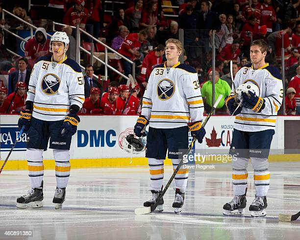 Joel Armia of the Buffalo Sabres lines up for the national anthem with teammates Mark Pysyk and Nikita Zadorov for his first NHL game against the...