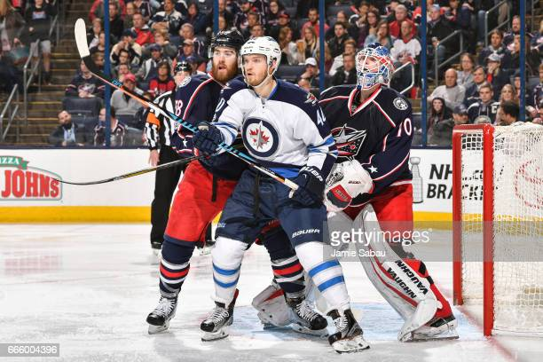 Joel Armia of the Winnipeg Jets battles for position with David Savard of the Columbus Blue Jackets in front of goaltender Joonas Korpisalo of the...