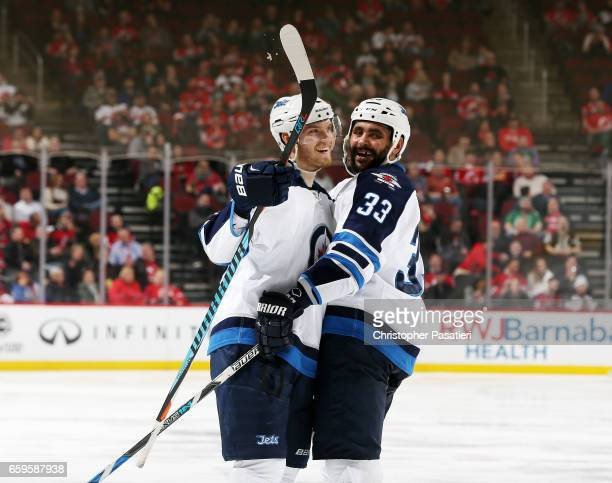 Joel Armia of the Winnipeg Jets is congratulated by Dustin Byfuglien after scoring the tying goal in the third period against the New Jersey Devils...