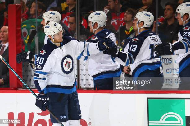 Joel Armia of the Winnipeg Jets is congratulated by his teammates after scoring a goal against the New Jersey Devils during the game at Prudential...