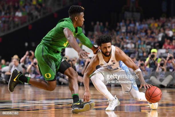 Joel Berry II of the North Carolina Tar Heels dribbles the ball as Dylan Ennis of the Oregon Ducks runs up to him during the 2017 NCAA Men's Final...