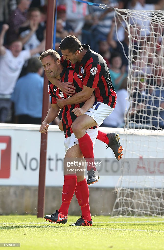 Joel Byron (L) of Preston North End is congratulated by team mate John Mousinho after scoring their third goal during the Sky Bet League One match between Coventry City and Preston North End at Sixfields Stadium on August 25, 2013 in Northampton, England.