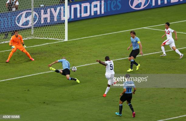 Joel Campbell of Costa Rica shoots and scores his team's first goal past Fernando Muslera of Uruguay during the 2014 FIFA World Cup Brazil Group D...