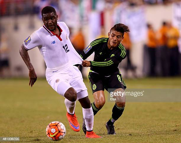 Joel Campbell of Costa Rica tries to get around Jonathan do Santos of Mexico during the quarterfinals of the 2015 CONCACAF Gold Cup at MetLife...