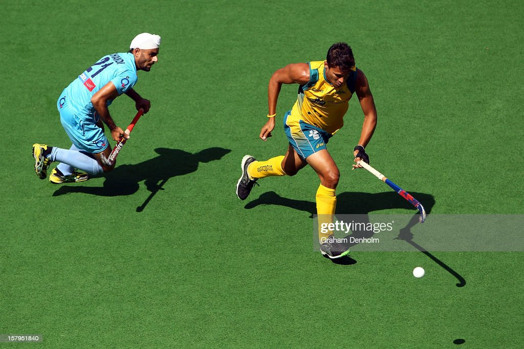 Joel Carroll of Australia (R) makes a break past Gurwinder Singh Chandi of India during the match between Australia and India during day five of the 2012 Champions Trophy at the State Netball and Hockey Centre on December 8, 2012 in Melbourne, Australia.