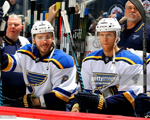 Joel Edmundson and Carl Gunnarsson of the St Louis Blues look on from the bench prior to puck drop against the Winnipeg Jets at the MTS Centre on...