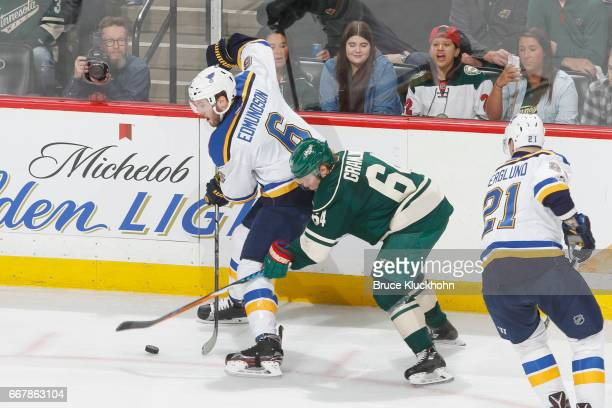 Joel Edmundson of the St Louis Blues controls the puck with Mikael Granlund of the Minnesota Wild defending in Game One of the Western Conference...