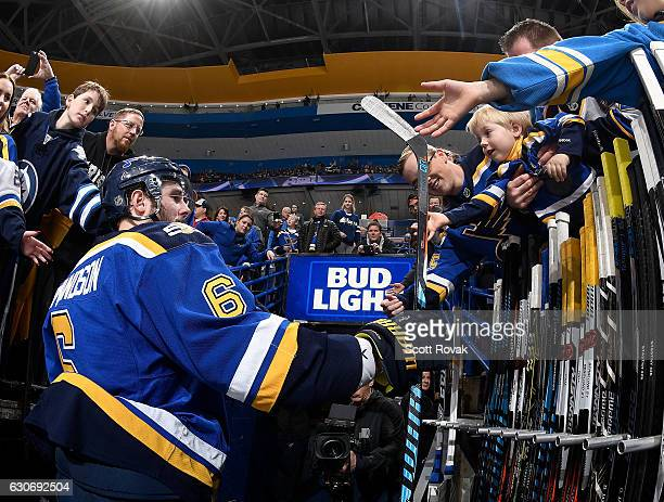 Joel Edmundson of the St Louis Blues gives a stick to a fan prior to a game against the Nashville Predators on December 30 2016 at Scottrade Center...