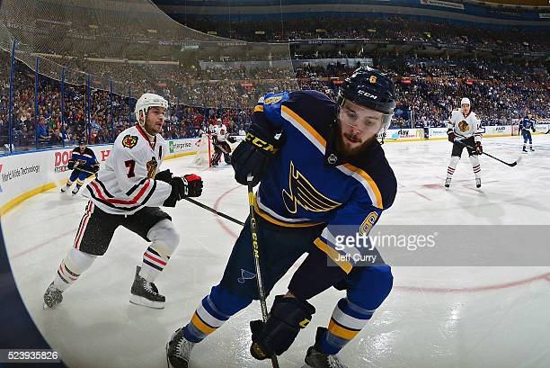 Joel Edmundson of the St Louis Blues skates against Brent Seabrook of the Chicago Blackhawks in Game Two of the Western Conference First Round during...