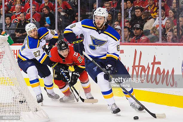 Joel Edmundson of the St Louis Blues skates with the puck past Mason Raymond of the Calgary Flames at Scotiabank Saddledome on October 13 2015 in...