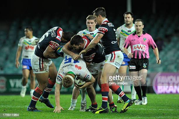 Joel Edwards of the Raiders receives a spear tackle of the Roosters' Luke O'Donnell and Isaac Liu during the round 22 NRL match between the Sydney...