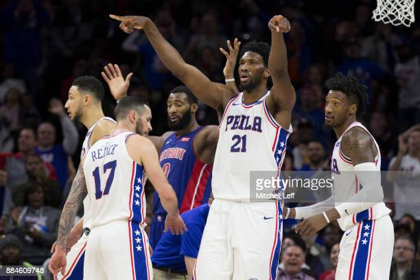 Joel Embiid Ben Simmons JJ Redick and Robert Covington of the Philadelphia 76ers react after Andre Drummond of the Detroit Pistons fouls out in the...